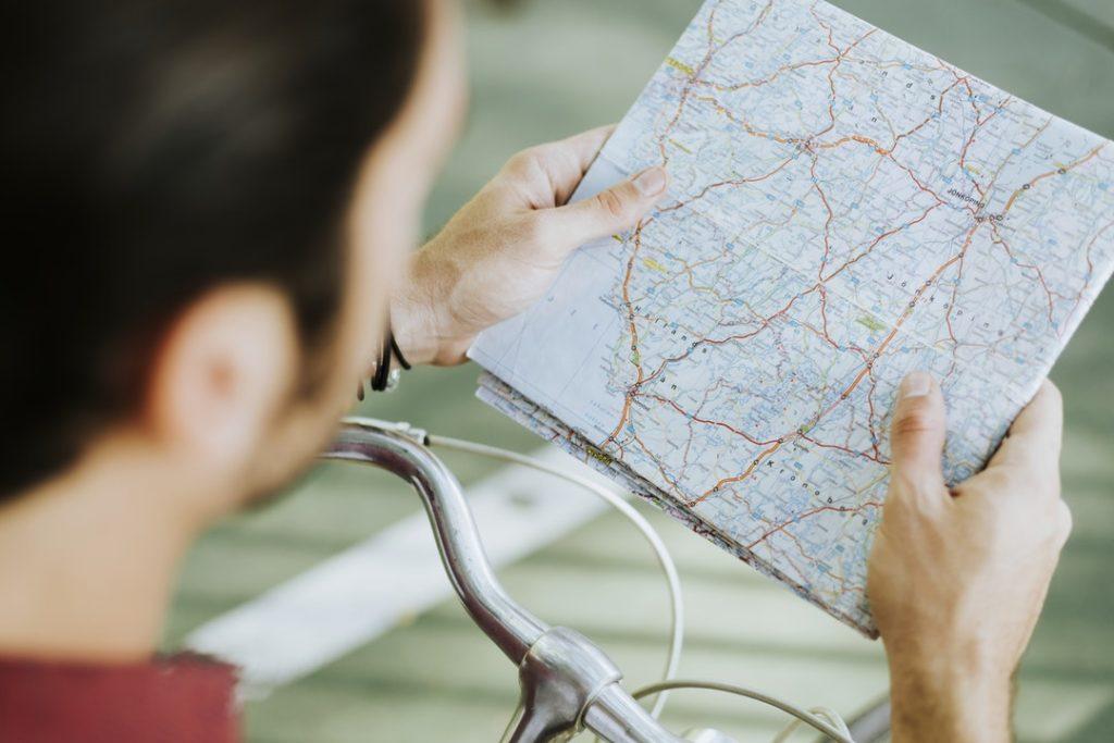 Hombre con bici mirando mapa